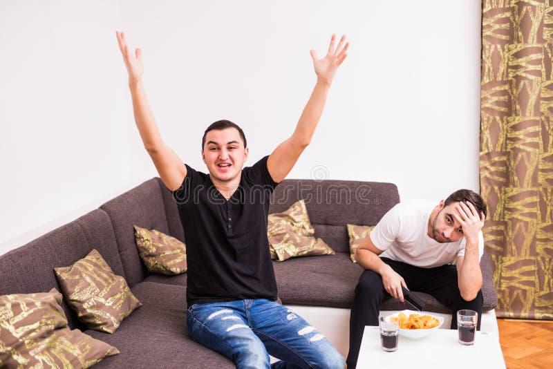 Kamratskap, sportar och underhållningbegrepp - lyckliga manliga vänner som hemma stöttar fotbollslaget En lycklig man, annan som  arkivfoton