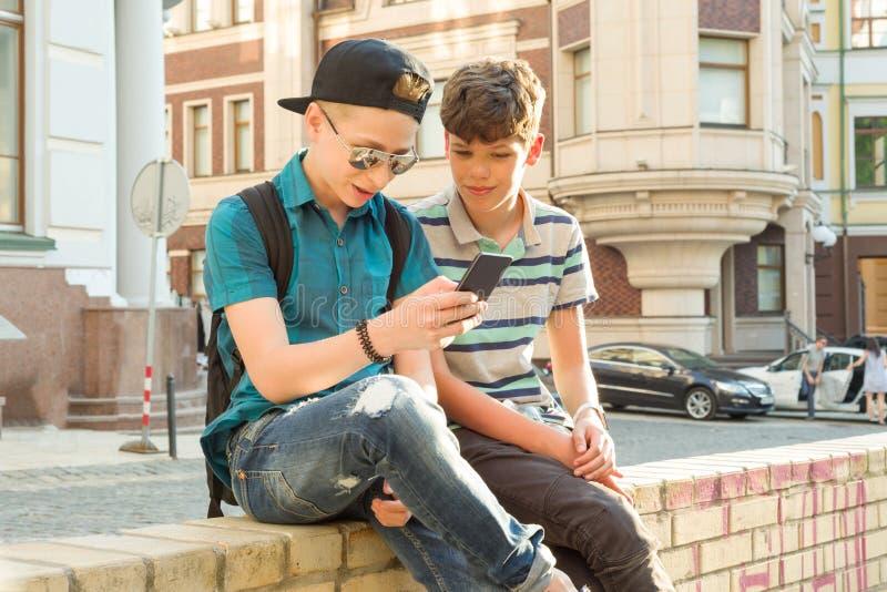 Kamratskapet och kommunikationen av två tonårs- pojkar är 13, 14 gamla år, stadsgatabakgrund royaltyfria bilder