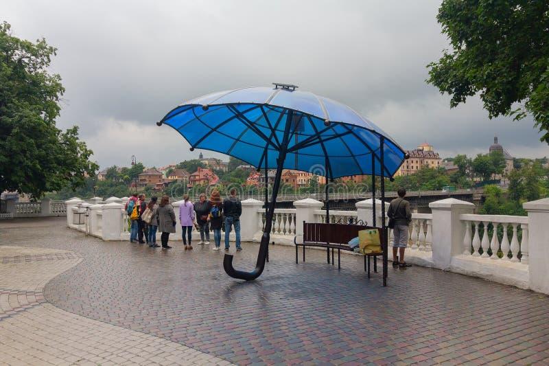 Kamyanets-Podolsky, Ukraine - June 30, 2018: Tourists on a rainy day by the bridge royalty free stock photography