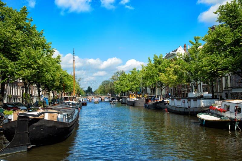 Kanäle und Dämme mit Booten von Amsterdam-Stadt lizenzfreies stockbild