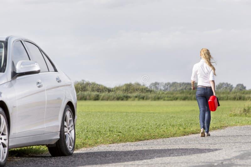 Kan den bakre sikten för den fulla längden av bärande gas för kvinnan lämna bak den brutna ner bilen på bygd arkivfoton