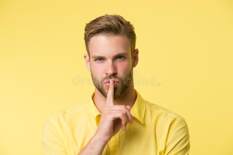 Kan du hålla hemligt Den stiliga mannen håller pekfingret vid hans kanter bakgrund är isolerad tyst white Hemligt berättelsebegre royaltyfria bilder