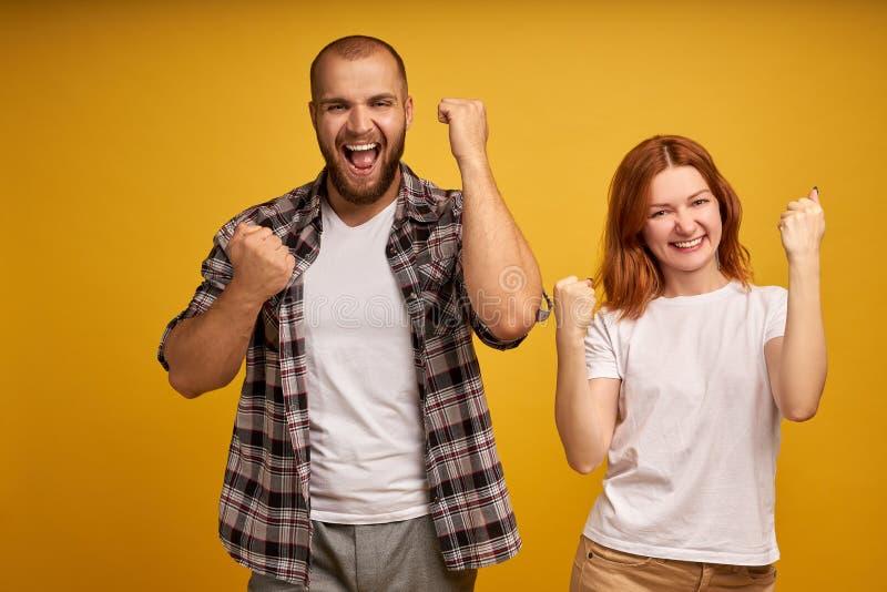 kan g?ra Det lyckade laget av coworkersknytnävar, firar seger, utropar positivt, ser säkert, har gladlynt royaltyfria foton
