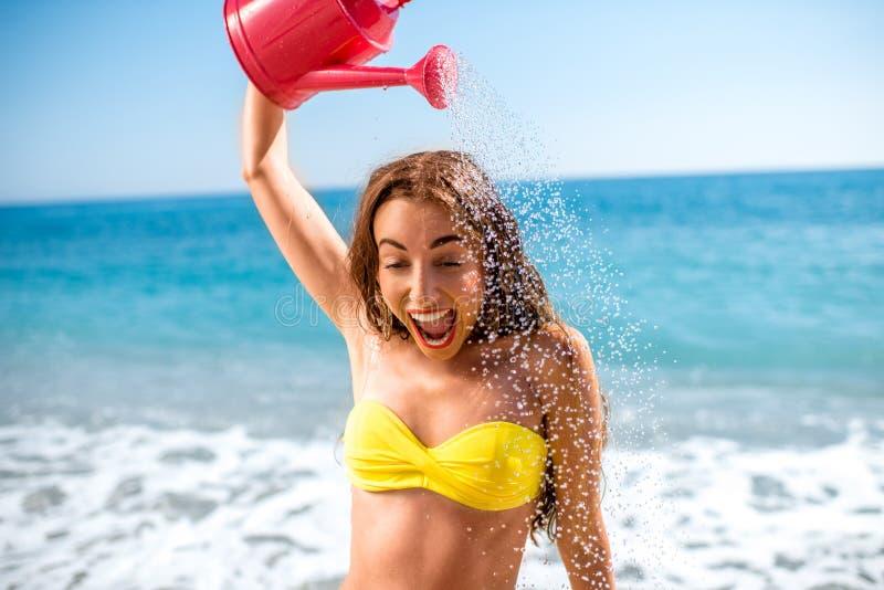 Kan hällande vatten för kvinnan från att bevattna på stranden arkivbild