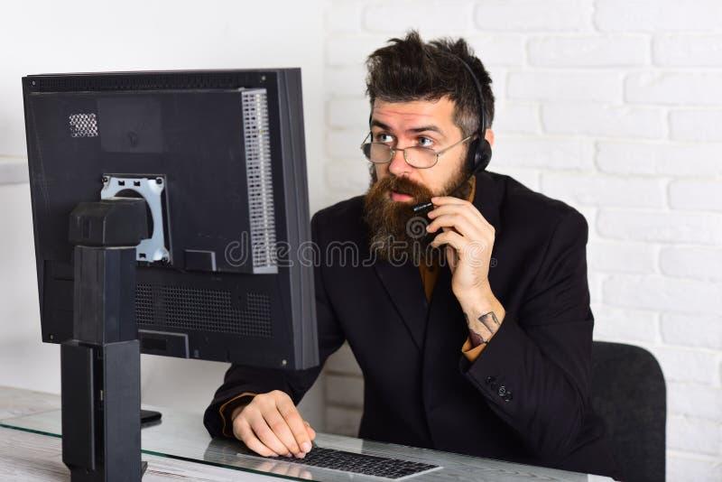 Kan ik u helpen Antwoordend de vraag van klanten Call centreexploitant op het werk Gebaarde mens die in bureau werken Mens stock foto's
