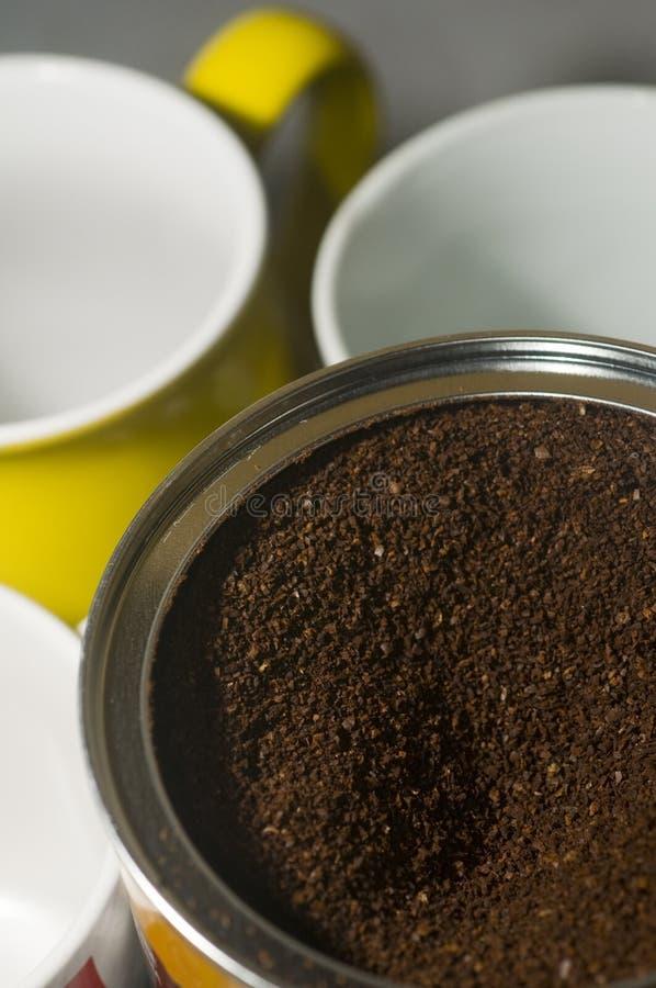 Kan van de bonen van de grondkoffie met mokken stock afbeeldingen