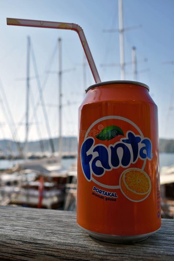 A kan van de oranje drank van Fanta met een stro op een houten plank met een vage achtergrond royalty-vrije stock afbeeldingen