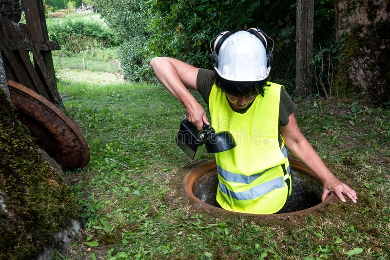 Kanał ściekowy naprawa pracuje w manhole kobieta pracownikiem zdjęcie stock