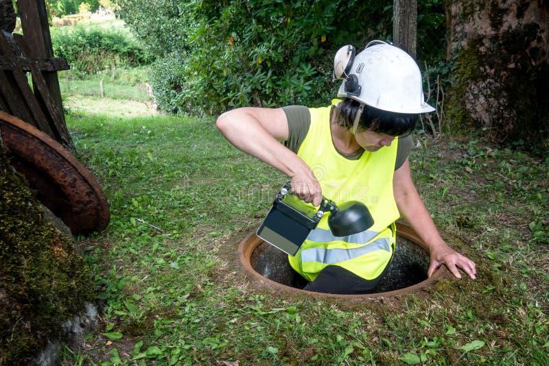 Kanał ściekowy naprawa pracuje w manhole kobieta pracownikiem obrazy stock