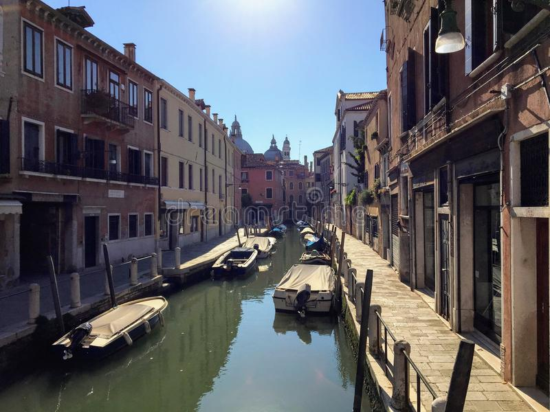Kanał w Wenecja, Włochy na spokojnym lato ranku Łodzie wykładają stronę kanał z niewiele ludymi chodzi obok kanału fotografia stock