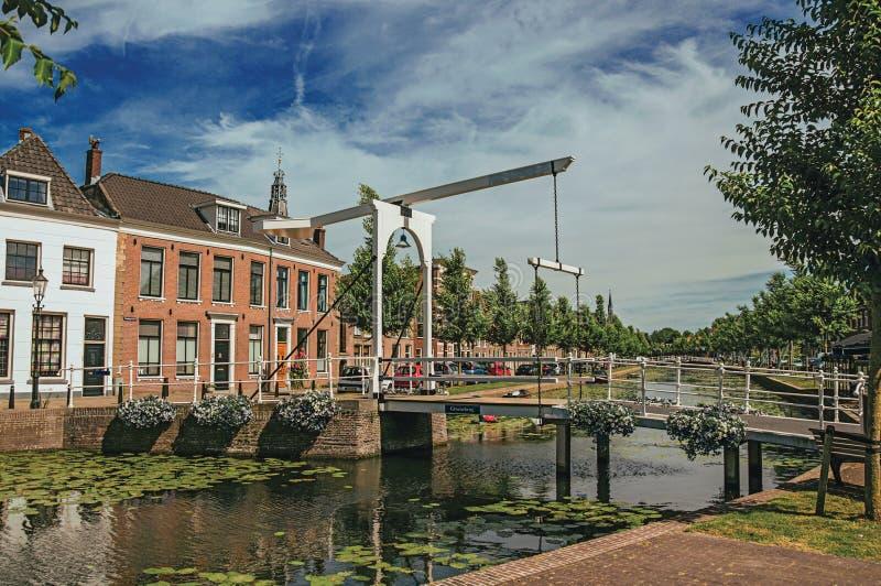 Kanał z ulicą na bankach na słonecznym dniu w Weesp, cegła domy i bascule most obraz stock