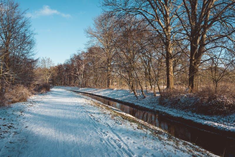 Kanaal die door de wintersneeuw overgaan stock afbeeldingen