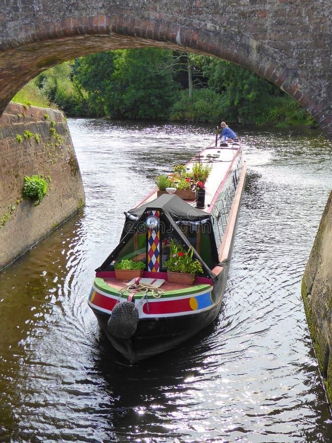 Kanaal die narrowboat onder brug overgaan stock afbeeldingen