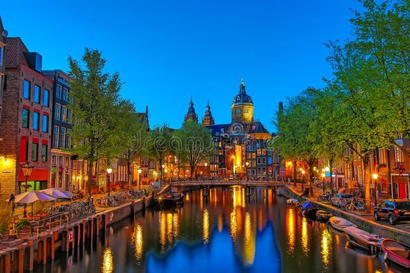 Kanaal en St Nicholas Church in Amsterdam bij schemering, Nederland Het beroemde oriëntatiepunt van Amsterdam dichtbij Centrale P stock fotografie