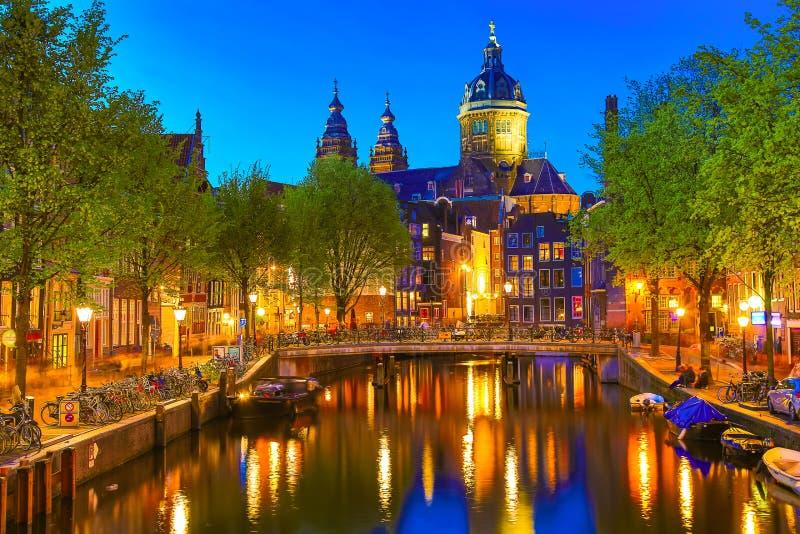 Kanaal en St Nicholas Church in Amsterdam bij schemering, Nederland Het beroemde oriëntatiepunt van Amsterdam dichtbij Centrale P stock afbeelding