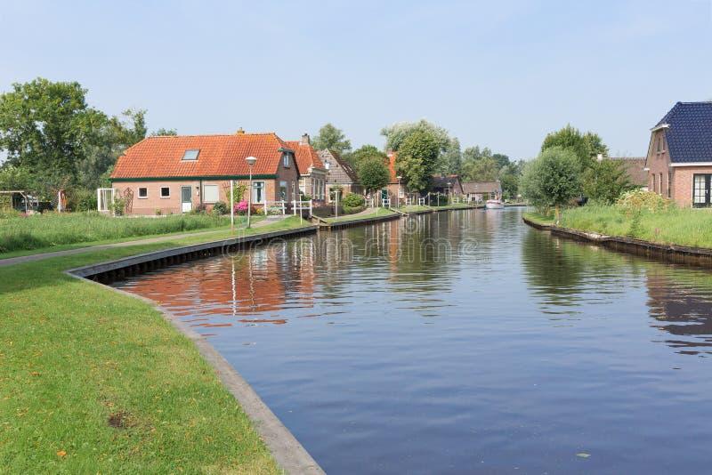 Kanaal met huizen in landelijk landschap van Nederland stock foto