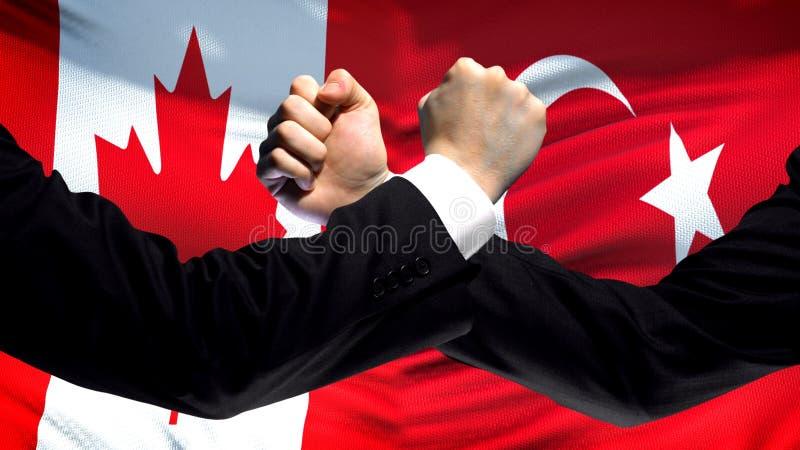 Kanada gegen die Türkei-Konfrontation, Landwiderspruch, Fäuste auf Flaggenhintergrund stockbild