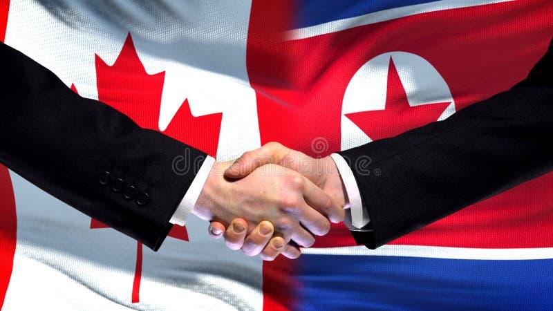 Kanada och Nordkorea handskakning, internationellt kamratskap, flaggabakgrund fotografering för bildbyråer