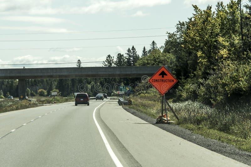 Kanada Ontario 09 09 2017 orange byggnadsarbetaretecken på vägen in i avståndet på trans. Kanada royaltyfri foto