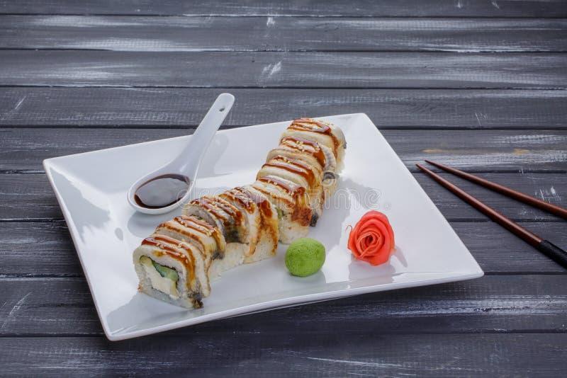 Kanada sushirullar med laxen, ålen, Philadelphia ost, avokadot och gurkan tjänade som på den vita plana plattan med pinnar Asiat  arkivfoton