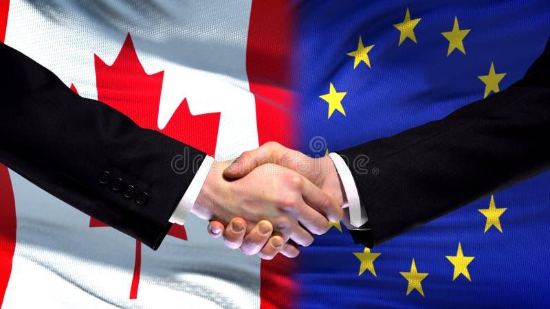 Kanada- und Gemeinschaftshändedruck, internationale Freundschaft, Flaggenhintergrund lizenzfreies stockfoto