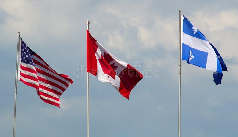 Kanada, USA och Quebec flaggor som vinkar i den molniga dagen för vind fotografering för bildbyråer