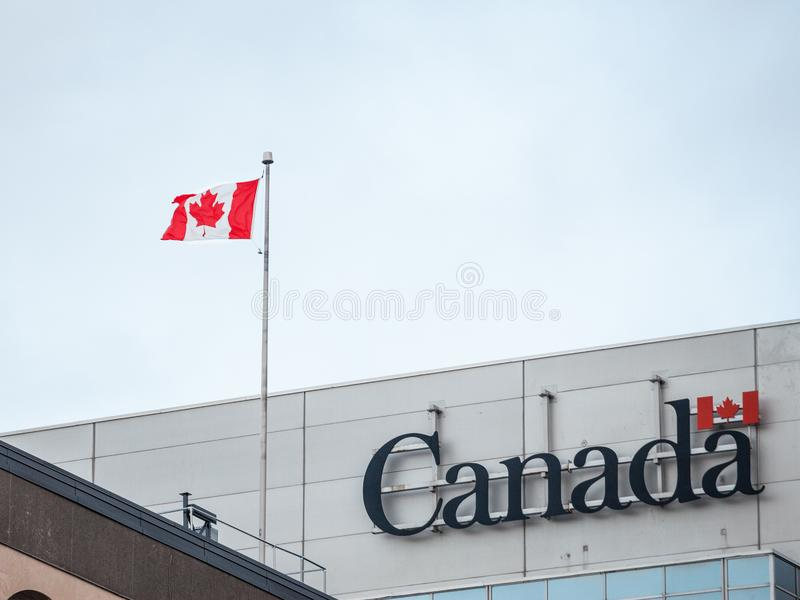 Kanada Wordmark, das offizielle Logo der kanadischen Regierung, auf einem Verwaltungsgebäude nahe bei einem kanadischen Flaggenau stockfoto