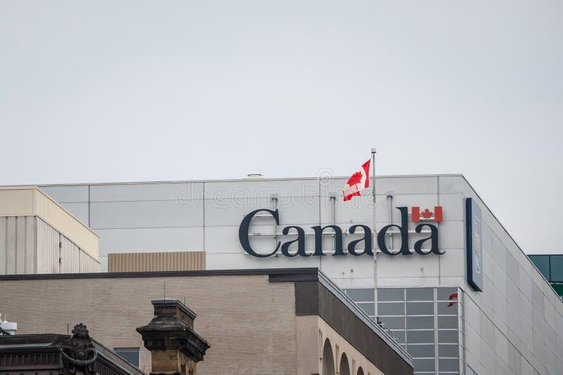 Kanada Wordmark, das offizielle Logo der kanadischen Regierung, auf einem Verwaltungsgeb?ude nahe bei einem kanadischen Flaggenau stockfoto