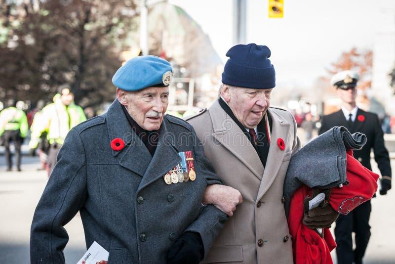 Kanadensisk krigsveteran för armé två, höga män, med deras medaljer och minnevallmo som betalar respekter till döda soldater arkivbilder