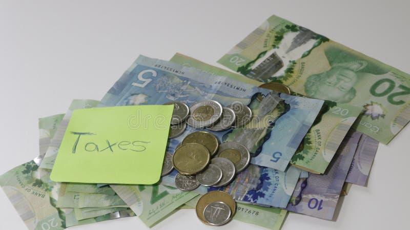 Kanadensisk skatteåterbäring som stavas med bokstavstegelplattor och anmärkningar för kanadensisk dollar royaltyfri fotografi