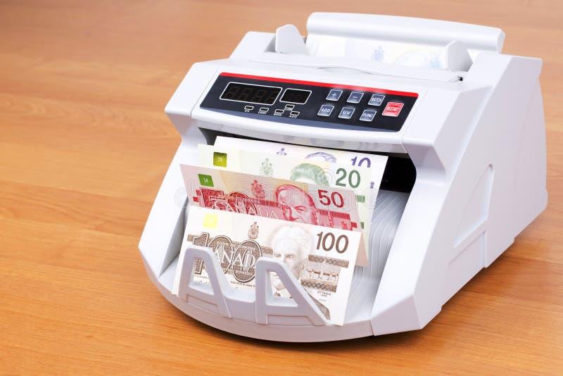 Kanadensiska dollar i en räknande maskin arkivfoto