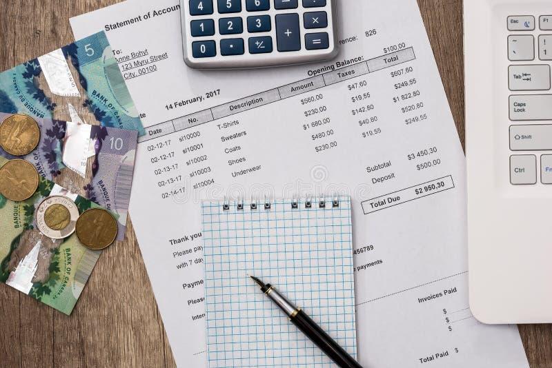 Kanadensiska pengar med bärbara datorn, dokumentet, pannan och räknemaskinen royaltyfria foton