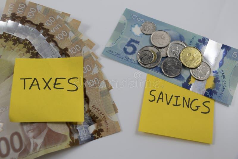 Kanadensiska pengar med en anmärkning som säger besparingar och skatter arkivbild