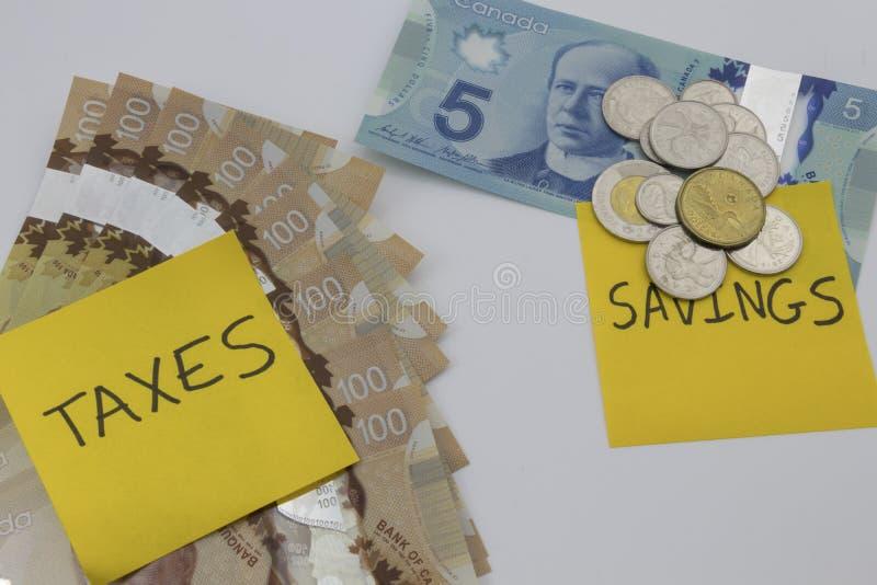 Kanadensiska pengar med en anmärkning som säger besparingar och skatter fotografering för bildbyråer