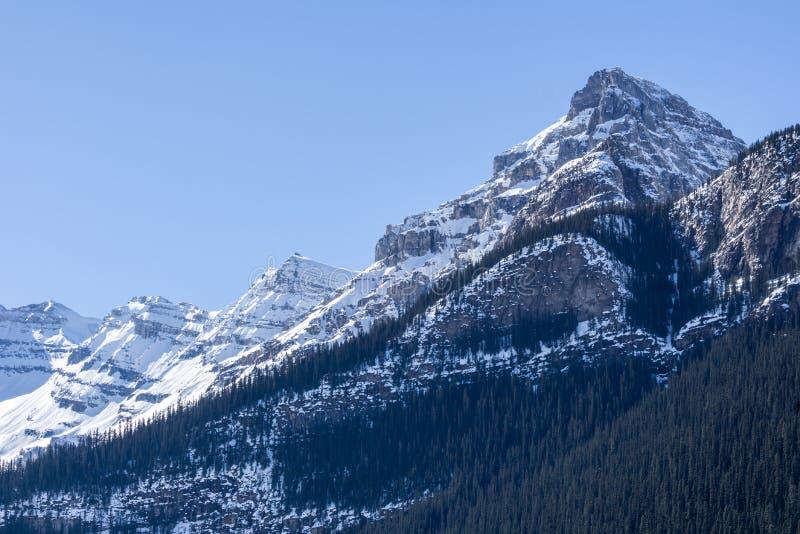 Kanadensiska steniga berg med klar himmel för insnöad Alberta Canada tidig vår arkivfoto