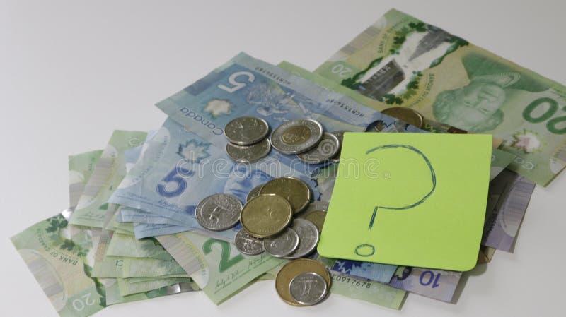Kanadische Geldverbreitung auf Tabelle mit einer klebrigen Anmerkung mit einem Fragezeichen Konzept der Finanzverwirrung und des  lizenzfreie stockfotos