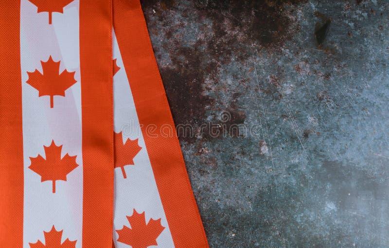 Kanadisches Rot und weiße Flagge gegen dunklen rustikalen Hintergrund für Kanada-Tagesfeier und -Nationalfeiertage stockfotos