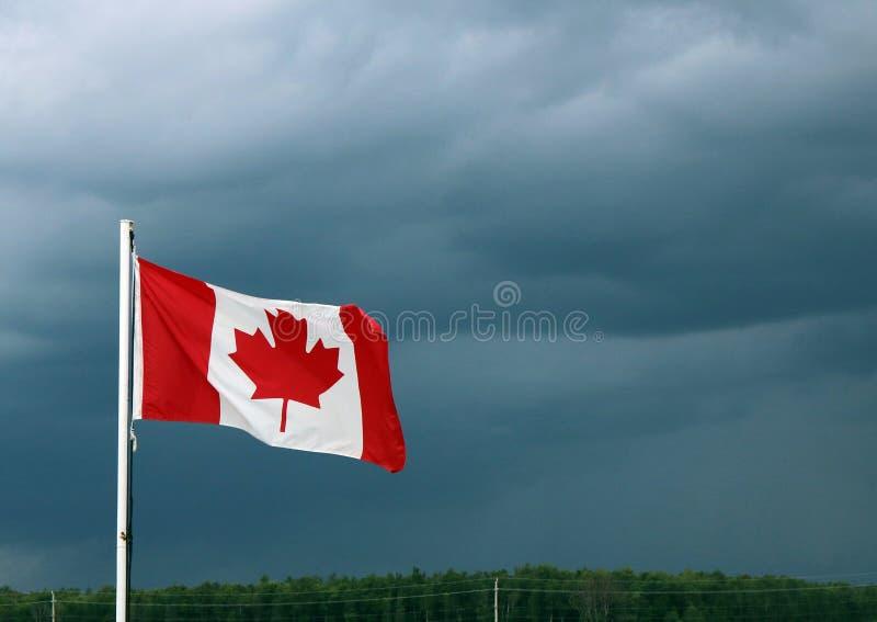 Kanadyjczyk flaga Macha Naprzeciw Ciemnych burz chmur zdjęcia royalty free