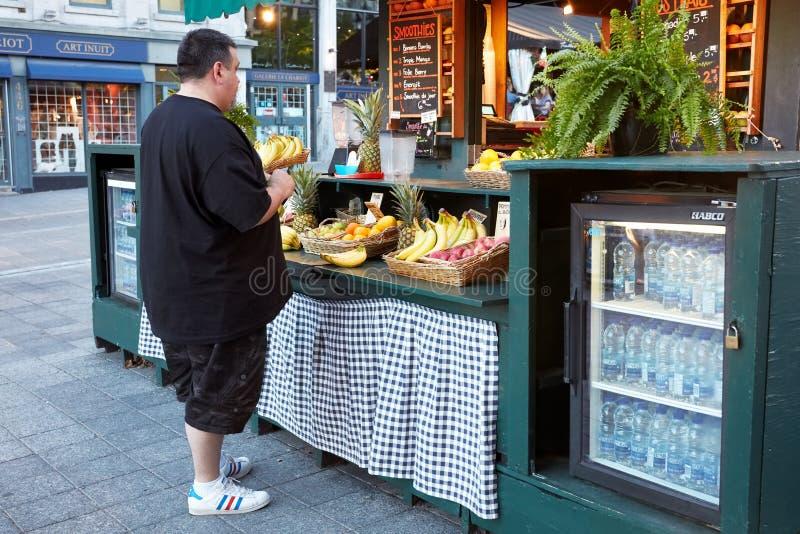 Kanadyjski z nadwagą wieka średniego mężczyzny zakupy od plenerowego owocowego soku baru z różnorodnymi owoc na kontuarze obraz stock