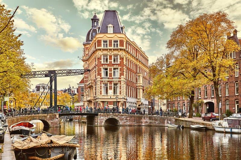 Kanal i floden Amstel för Amsterdam Nederländernahus royaltyfria bilder
