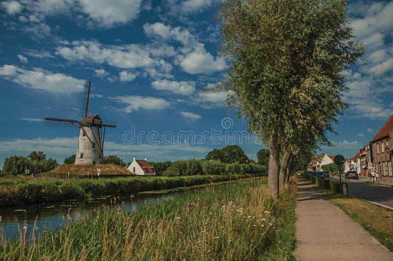 Kanal med den gamla väderkvarnen och trän i ljuset för sen eftermiddag och den blåa himlen, bredvid trottoaren och Damme royaltyfri fotografi