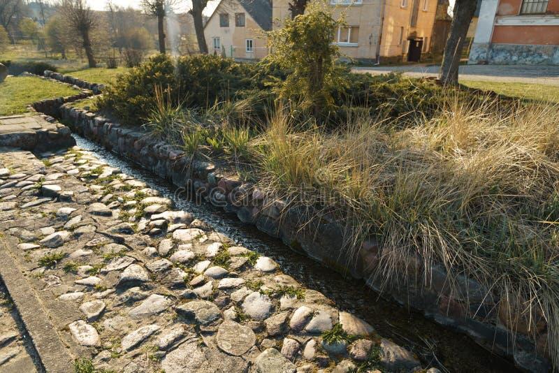 Kanal med vårvatten i staden Sabile i Lettland royaltyfri foto