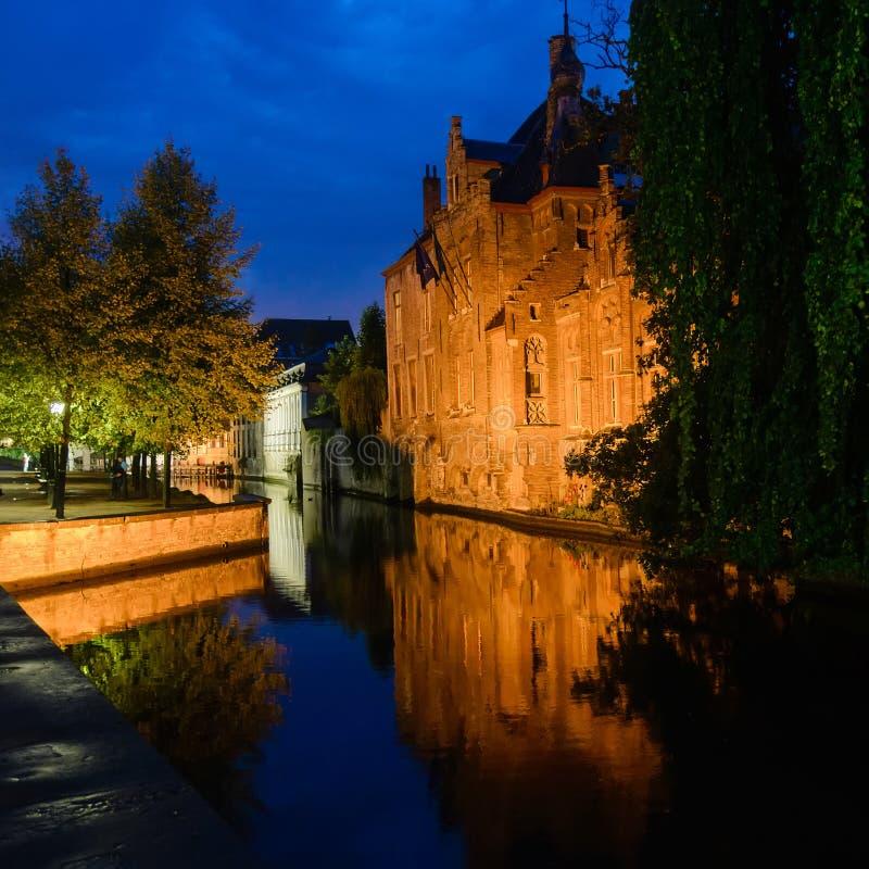 Kanal och gamla hus på natten i Brugge royaltyfria foton