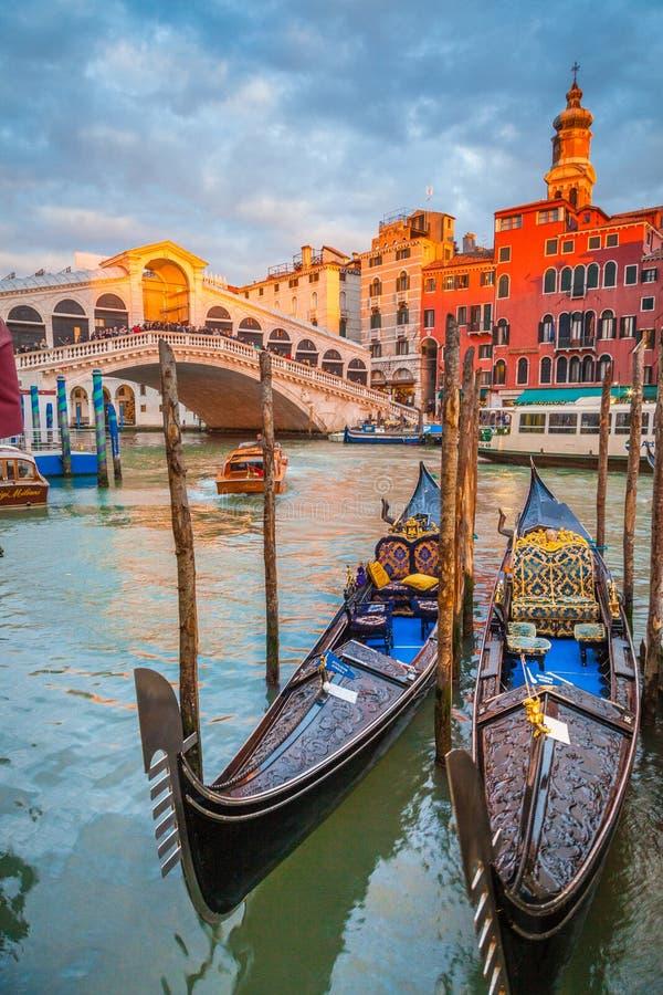 Kanal som är stor med gondoler och den Rialto bron på solnedgången, Venedig, Italien royaltyfria bilder