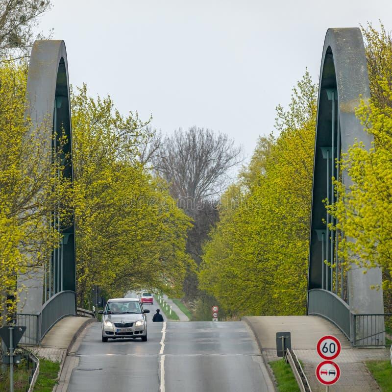 Kanalbrücke im Bogenbau mit den gelben und grünen blühenden Birken am Rand der Straße hergestellt vom grauen Asphalt stockfoto