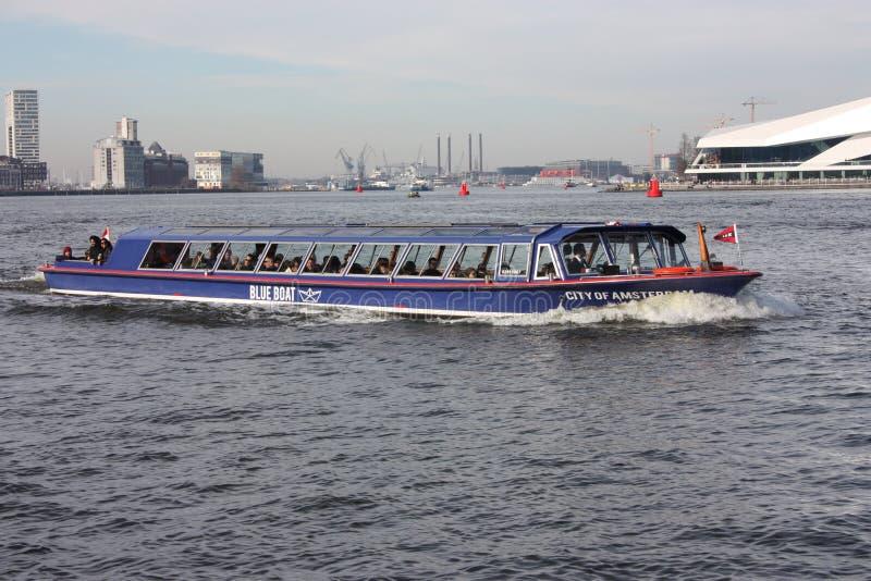 Kanalen eller floden framme av den amsterdam centralstationen, anv?nt som en kollektivtrafik f?r pendlare och turister royaltyfri fotografi