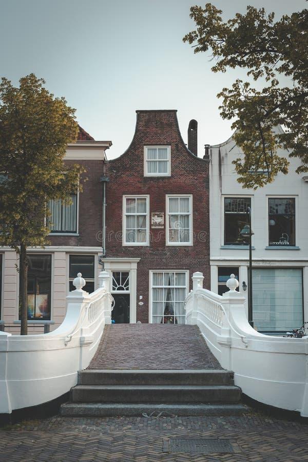 Kanalhus i delftfajans och härlig vit bro på Voorstraaten royaltyfri bild
