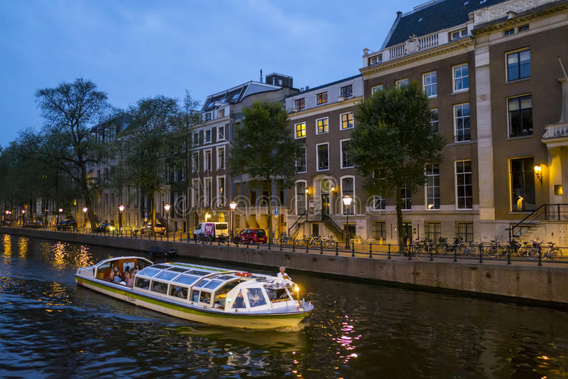 Kanalkryssning i staden av Amsterdam vid natt - AMSTERDAM - NEDERLÄNDERNA - JULI 20, 2017 arkivbilder