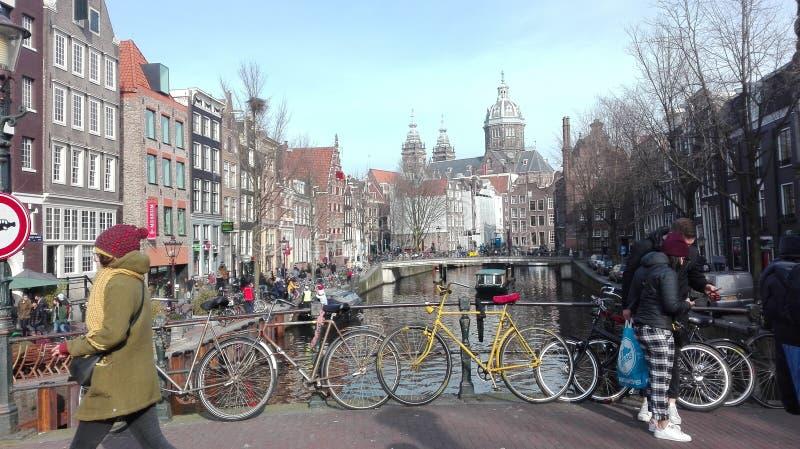 Kanalsikt på Amsterdam och den gula cykeln arkivbilder