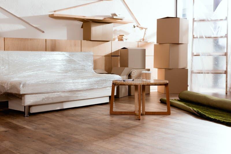 kanapa, stół, staczał się dywan i kartony obrazy stock